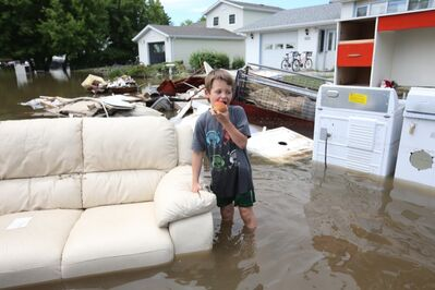 Six-year-old Aiden Sanderson eats an apple while walking through the flood water on Second Street in the community of Reston on Wednesday. Several families whose homes were flooded over the weekend were in the midst of cleaning up when Tuesday evenings storm caused flooding again.