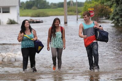 Daveena Zorn, Natasha Morrison and Garrett Adcock walk along a flooded street in the community of Reston after Adcock's vehicle stalled on a flooded road outside of town on Wednesday. The trio were headed home from Zorn's grad which was the previous day and had to walk to Reston when their vehicle became flooded.