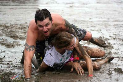 Making the best of a rainy situation, two festivalgoers have a mud fight at Dauphin's Countryfest on Friday afternoon. Campers saw rain come and go on Thursday and Friday.