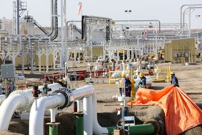 Workers are framed by pipes and structures at the Enbridge Cromer Terminal just north of Cromer.