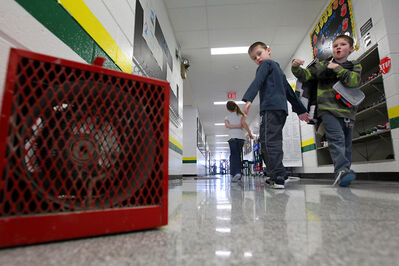 Students walk to class past a portable heater at Green Acres School on Tuesday after the school's heating system malfunctioned.