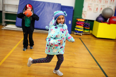 Green Acres School student Mahlet Mengistu plays in gym class while wearing her winter jacket and toque, while Owen Haight sports a toque and a hoodie on Tuesday.