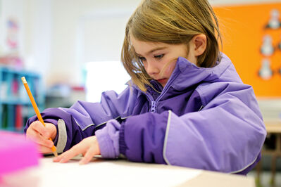 Kirsten Rogers in Susan Wright's Grade 1-2 class at Green Acres School works on an assignment while wearing her winter jacket on Tuesday after the school's heating system malfunctioned. Industrial heaters were set up throughout the school to help keep the temperatures tolerable.