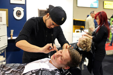 Kevin Soriano gives Marcus Oag a straight razor shave at the Westeel Smoothwall Barber Shop, part of Westeel's exhibit at Manitoba Ag Days.