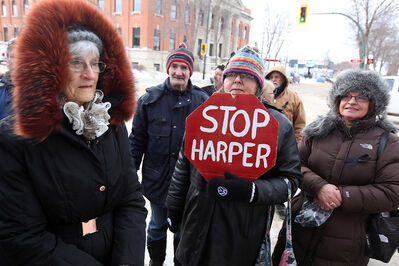 "Mary Hutchings holds a ""Stop Harper"" placard while gathering with veterans and supporters outside the Veterans Affairs office in Brandon on Friday."