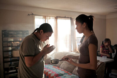 Stephen Bunn, a Grade 11 student at Crocus Plains Regional Secondary School, washes smoke from burning sage held by his sister Tyanna over his face and body while demonstrating a traditional smudge in his family's home in Brandon's south end after school on Thursday. Bunn has faced disciplinary action at school for smudging before class.