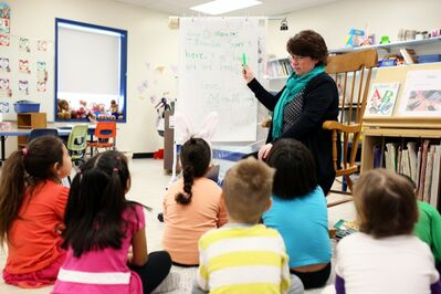 Carole McCurry engages her students in a spelling and reading exercise during full-day kindergarten at George Fitton School.