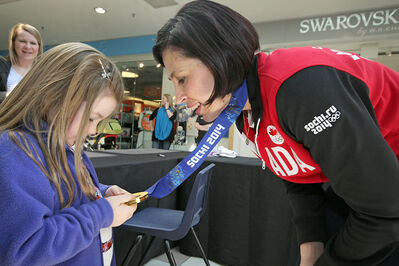 Six-year-old Ella Howe takes a close look at the gold medal won by former Brandon resident Jill Officer who was signing autographs at Shoppers Mall on Saturday. Officer was part of Canada's women's curling team at the 2014 Olympic Winter Games in Sochi, Russia.