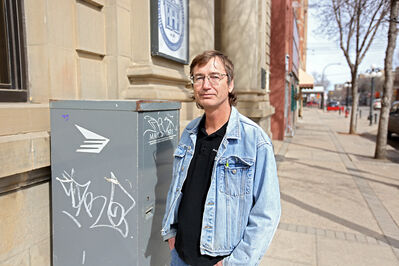 Gerard Wade, owner of People's Market Place on 13th Street, points out graffiti on a Canada Post box on Rosser Avenue in downtown Brandon on  a recent afternoon.  LEFT: Graffiti covers garbage bins behind  businesses on  Seventh Street and a  wall in an alleyway  bordering Rosser Avenue  in downtown Brandon.