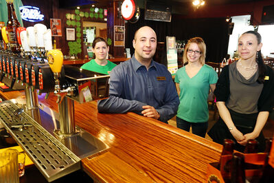The Dock on Princess general manager Jamie Munro, foreground — pictured with employees Erin Wells, Chantelle Roblin and Jessica O'Connell — plans to keep regular hours on Good Friday. Munro expects being open on the bar and eatery's busiest day of the week should help offset the added costs of paying staff time and a half for working the statutory holiday.