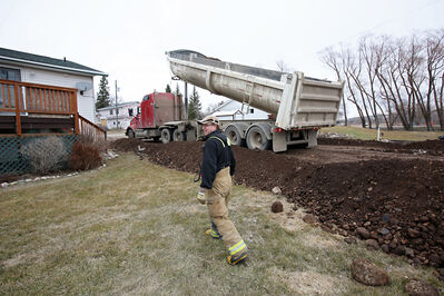 A dump truck empties a load of dirt as a dike is built surrounding a low-lying home and the lift station for Birtle to protect residents from the rising Birdtail Creek on Saturday.