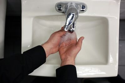 An employee at a restaurant in Brandon washes his hands prior to working in the kitchen.