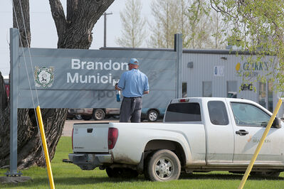An airport employee removes lettering from the Brandon Municipal Airport sign on Tuesday. New signage, honouring aviation pioneer Ed McGill, should be up next week. A new sign near the highway will also be erected.