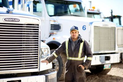 Colby Taylor, Owner of Taylor Oilfield Services just outside Melita, stands in front of part of his fleet of vacuum trucks.