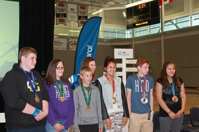 Hughes poses with students wearing her Olympic medals during her stop in Brandon on Friday.