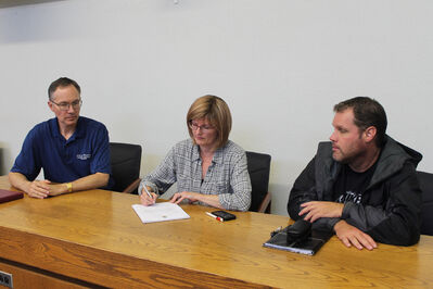 Mayor Shari Decter Hirst signs papers declaring a state of local emergency for Brandon, while emergency coordinator Brian Kayes and general manager of operations Rod Sage watch.