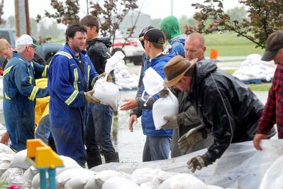 Volunteers help build a sandbag dike around homes in the town of Reston in southwestern Manitoba on Sunday after incessant rainfall creating overland flooding in the community. Reston was also hit hard by flooding just over a year ago.