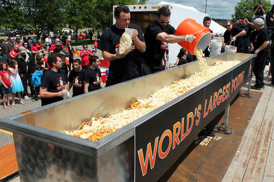 Joe Beeverz Bar and Grill staff add cheese curds to their world record-breaking poutine at the Riverbank Discovery Centre on Canada Day.