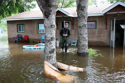 Josh Kitto walks through floodwater surrounding apartments owned by his parents in Virden on Monday after the rising Gopher Creek inundated the homes over the weekend, forcing the evacuation of residents.