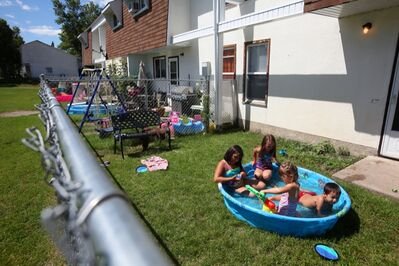 Children play in a kiddie pool in the backyard of a home in the Hillside Town Homes complex in Brandon's east end on Friday afternoon.  Residents in the normally safe neighbourhood have been rattled by a series of bizarre break-ins — in which nothing was taken — that some believe are the work of on man targeting single mothers.