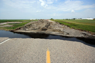 A small cut in Highway 21 south of Hartney to alleviate flooding pressure ended in a massive hole after the water ripped away the culvert and washed away the road.