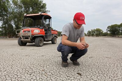 Kyle Ratz, Superintendent for the Wheat City Golf Course, examines a silt covered fairway on the course on Tuesday after the flood water had receded.