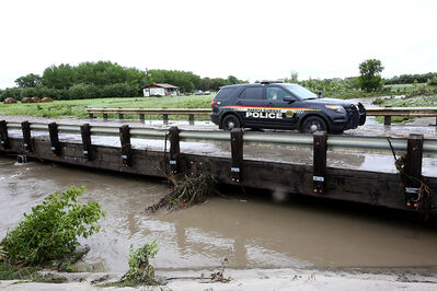 A Dakota Ojibway Police Service vehicle crosses a bridge over a swollen creek after checking on evacuated houses on the north side of Sioux Valley Dakota Nation in this June photo. What was supposed to be a short stay at a Brandon hotel is now in its third month for many Sioux Valley flood evacuees.