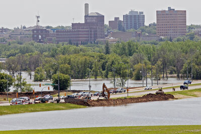 Dike work continues on 18th Street at Grand Valley Road (now covered in water) on Friday afternoon in preparation for the rising Assiniboine River's crest expected to come Saturday. The river has risen noticeably since this photo was taken.