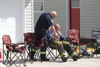 A firefighter takes a much-needed oxygen break Friday morning while the fire continues to burn. (Tim Smith/Brandon Sun)