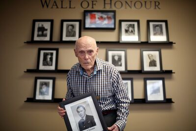 """Riverheights Terrace resident Doug Christie holds an old portrait of himself that sits on the retirement home's Wall of Honour, commemorating veterans that reside there, in this April photo. Christie, who served as a tail gunner during the Second World War, will be selling and signing copies of his new memoir, """"Some Experience,"""" at the Commonwealth Air Training Plan Museum on Remembrance Day at 2 p.m."""