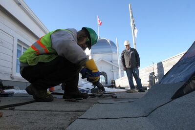 Display Building No. II restoration project manager Daryl Knight watches Jordan McGregor, a production foreman with Flynn Canada, torch a granular cap sheet on the top of the Dome Building on Wednesday afternoon.