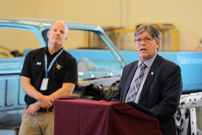 Education and Training Minister Ian Wishart speaks as Crocus Plains Regional Secondary School principal Chad Cobbe listens during an announcement at the local high school's collision repair shop on Thursday morning. Wishart announced that the province would commit $347,453 to CPRSS's Collision Repair Program.