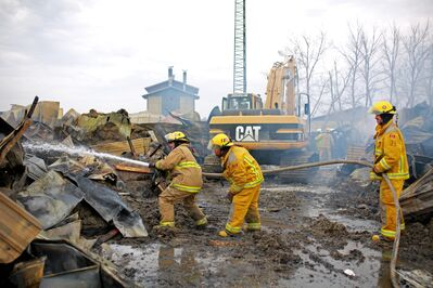 Firefighters extinguish a hot spot in the ruins of the mechanic shop.