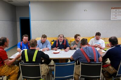 Firefighters eat a big lunch made by women from Decker Hutterite Colony after battling a fire that destroyed the mechanic shop on the colony on Monday morning.