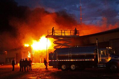 Members of Decker Hutterite Colony battle a fire in their large mechanic shop early Monday morning. No one was injured in the blaze, which is believed to have been caused by a lightning strike.