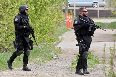 Members of Brandon Police Service's Tactical Response Unit and other members search for a suspect on Third Street near Rosser Avenue after a chase on Thursday afternoon.