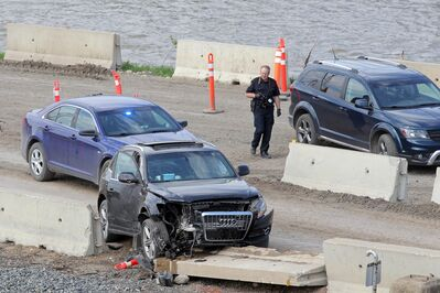 A Brandon Police Service Forensic Identification Unit member photographs a damaged vehicle involved in a police chase on Thursday afternoon. A suspect crashed their vehicle into a barrier in the CP Rail yard and took off on foot before being eventually captured on Third Street between Rosser Avenue and Pacific Avenue.