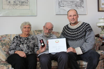 Errol Black (centre) and his wife Margaret Black accept the Queen Elizabeth Diamond Jubilee Medal and certificate from Brandon East MLA Drew Caldwell on Saturday.