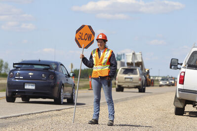 Brandon Sun 30052012 Sam Shamanski with Tri-Wave Construction warns motorists of construction on Highway 10 just north of Forrest on Wednesday afternoon. The highway is undergoing an improvement project which includes milling and repaving approximately 15 km's of road surface. (Tim Smith/Brandon Sun)