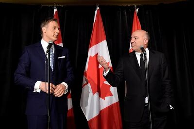 Conservative Party leadership candiidate Maxime Bernier (left) looks on as Kevin O'Leary address a news conference in Toronto, Wednesday, April 26, 2017, after it was announced that O'Leary had quit the leadership race. THE CANADIAN PRESS/Nathan Denette