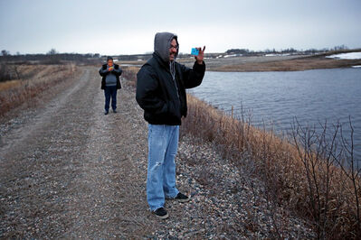 Troy Richard of Waywayseecappo First Nation takes photos of the high water butting up against an old rail line embankment at the first nation late Saturday evening. A frozen culvert has caused water from a tributary of Birdtail Creek to build up at the embankment. According to a government issued flood bulletin  released Sunday morning the embankment is failing which will lead to a surge of water that will affect communities downstream such as Waywayseecappo, Rossburn, Birtile, Miniota and Birdtail Sioux First Nation. (Tim Smith/Brandon Sun)