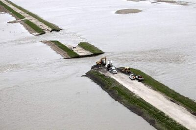 Crews try to shore up a breach in the Portage Diversion during flooding in 2011. Farmers say they are still paying costs associated with the disaster.