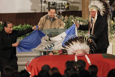 Harper's son, Bruce, (left), Grand Chief Derek Nepinak (right) and Jonathan Flett place an Island Lake flag on Harper's casket.