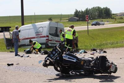 Paramedics give medical attention to one of the people involved in a collision between a motorcycle and a cube van at the intersection of Highway 1 and Highway 270 just west of Brandon on July 12.