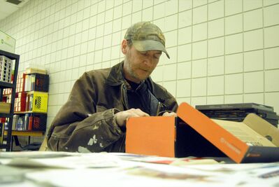 Tom Vogt sifts through postcards at the Prairie Mountain Philatelic Society's stamp sale at the Keystone Centre on Saturday.
