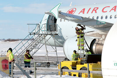 Ground crew members work to refuel an Air Canada A320 jet at the Brandon Municipal Airport after it was diverted from Winnipeg on Wednesday.