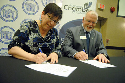 Gloria Spence of the Aboriginal Chamber of Commerce signs a memorandum of understanding with Brandon Chamber of Commerce president Terry Burgess, wherein the local chamber commits to supporting aboriginal business development.
