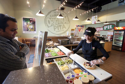 """An employee serves up a pita to a waiting customer at Brandon's Pita Pit at 658 18th St. on Friday afternoon. The local pita shop is offering 10 pitas under 500 calories this month as part of its second annual """"resolution solution"""" campaign."""