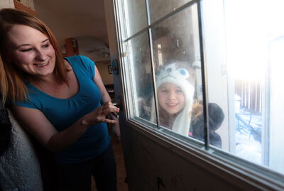 Robin Leslie greets her daughter Abby, 6, at the door after school on Tuesday afternoon. Abby's parents have tried to get her a spot on a school bus, but the Brandon School Division says the family doesn't live far enough away from Kirkcaldy Heights School to qualify.