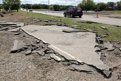 A section of asphalt road surface lies in the ditch along First Street North near Dinsdale Park on Monday, after being lifted from its place by floodwaters over the past month.